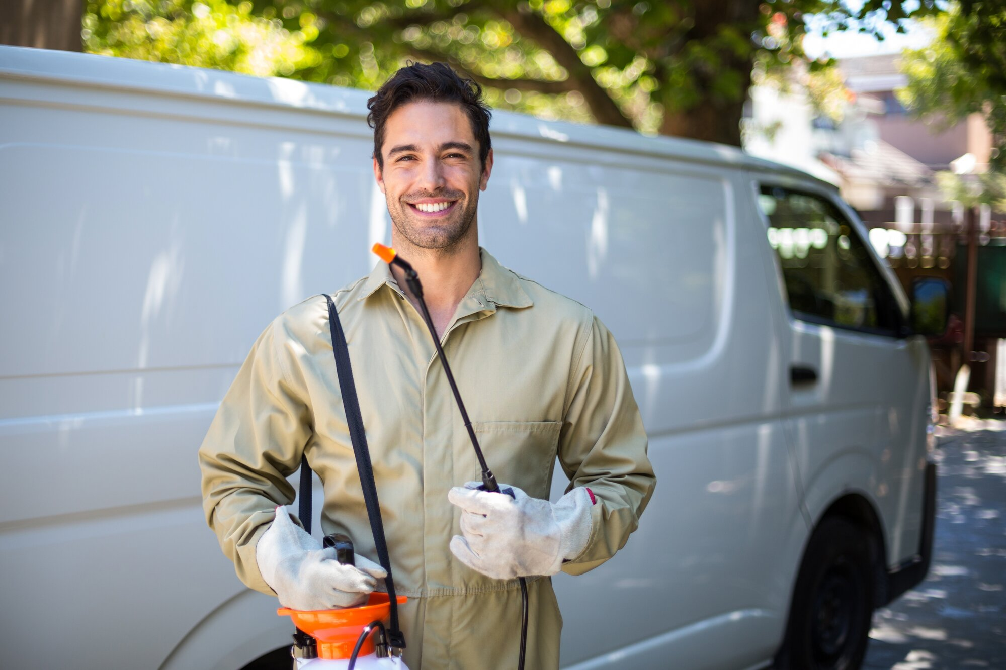 Smiling worker with pesticide sprayer and van on the back